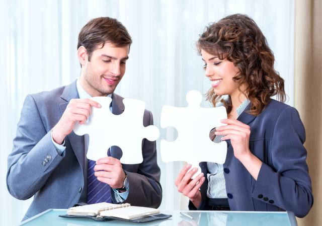 Young business people stitching the puzzle
