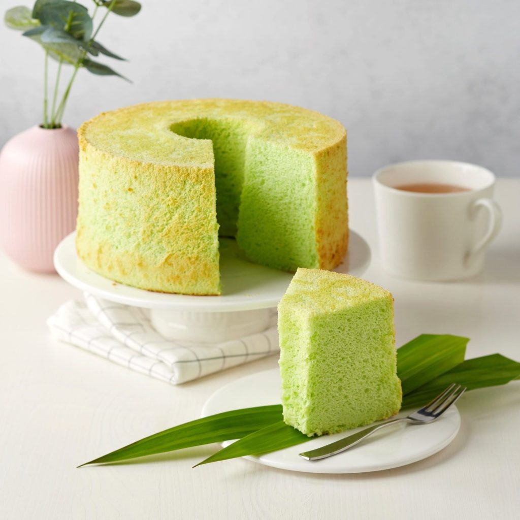 A piece of cake sitting on top of a green plate  Description automatically generated
